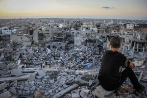 A Palestinian child sits above the ruins of his ruined home